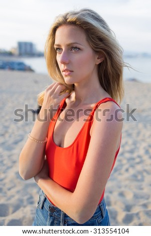 Portrait of young blonde hair charming woman standing alone on the beach waiting for someone, caucasian female with beautiful eyes posing for the camera near the sea in sunny summer evening - stock photo