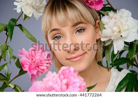 Portrait of young blonde pretty girl among flowers looking at camera, smiling over grey background.
