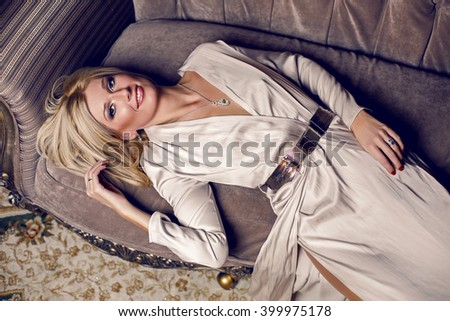 portrait of young blonde woman lying on the sofa in a long dress