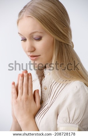 Portrait of young blonde woman praying, looking down. - stock photo