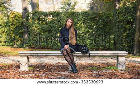 Portrait of young blonde woman sit on a bench outdoors in a park in autumn. Ducale Park - Parma, Italy.