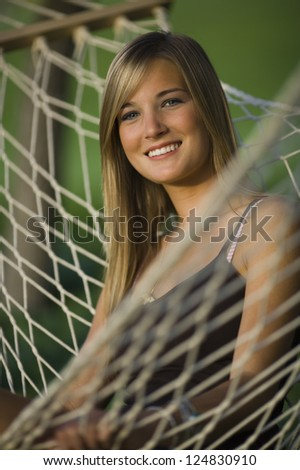 Portrait of young blonde woman sitting in hammock - stock photo