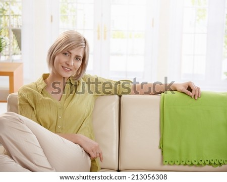 Portrait of young blonde woman sitting on sofa at home, looking at camera smiling. - stock photo