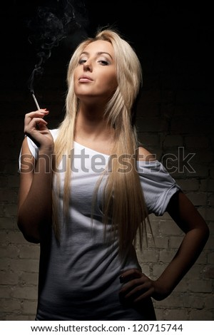 Portrait of young blonde woman with a cigarette on dark background - stock photo