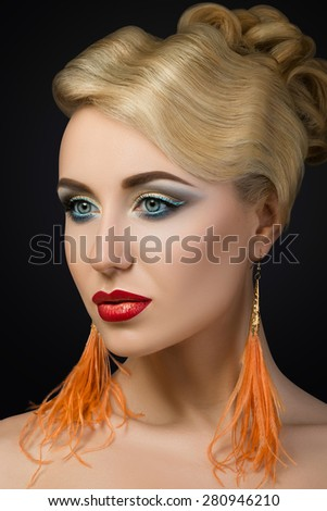 Portrait of young blonde woman with red lips and orange feather earrings. Fashion make-up details - stock photo