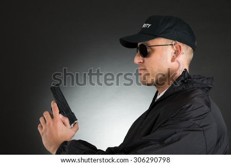 Portrait Of Young Bodyguard Holding Gun Over Black Background - stock photo