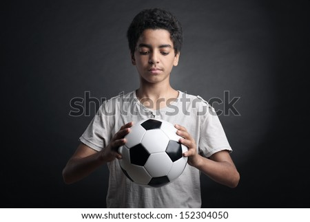 Portrait of young boy holding a soccer ball - stock photo