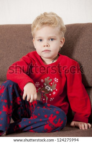 Portrait of young boy in pajama sitting on the sofa - stock photo