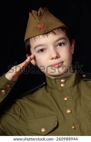 Portrait of young boy in Soviet military uniform on black background - stock photo