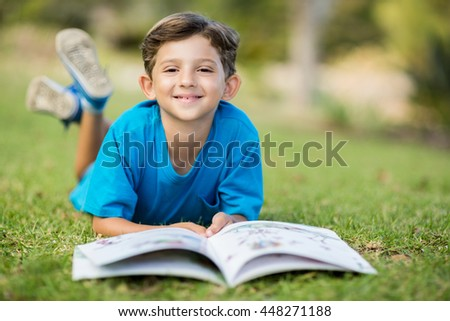 Portrait of young boy lying on grass with book in park