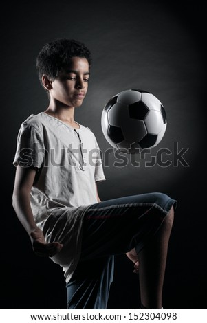 Portrait of young boy playing with a socce rball - stock photo