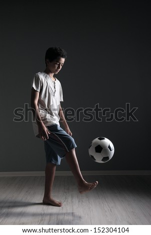Portrait of young boy playing with a soccer ball - stock photo