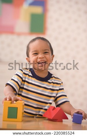 Portrait of young boy playing with blocks - stock photo