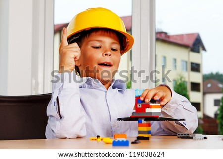 Portrait of young boy posing at home with lego in helmet - stock photo
