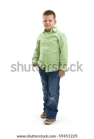 Portrait of young boy posing in green shirt and jeans, looking at camera, smiling. Isolated on white.