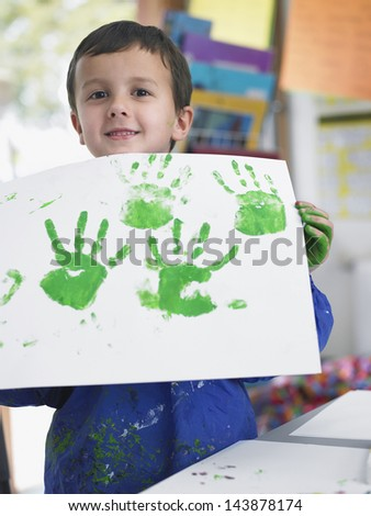 Portrait of young boy presenting his finger painting in art class - stock photo