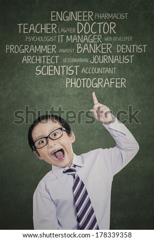 Portrait of young boy showing his aspirations on the blackboard - stock photo