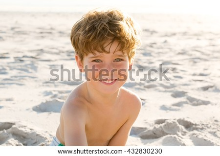 Portrait of young boy sitting on sand at beach and looking at camera. Little boy enjoying holiday at beach. Cute child playing at beach at sunset.