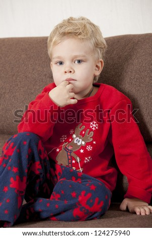 Portrait of young boy sitting on sofa in pajama - stock photo