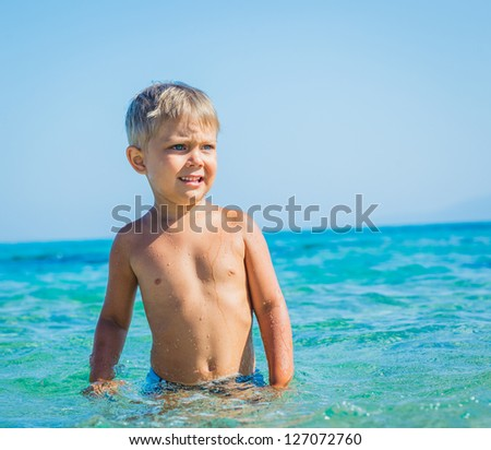 Portrait of young boy swimming in the transparent sea - stock photo