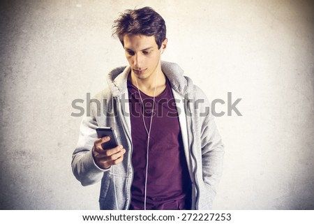 Portrait of young boy using mobile phone with headphones
