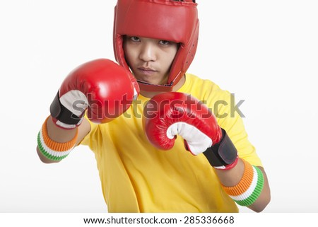 Portrait of young boy wearing boxing gloves and head protector ready for the match over white background