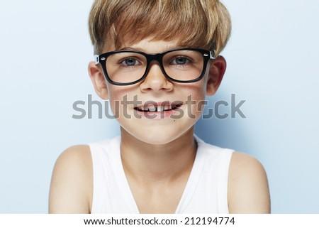 Portrait of young boy wearing glasses, studio  - stock photo