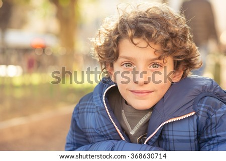 Portrait of young boy, winter dressed and looking at the camera.  - stock photo
