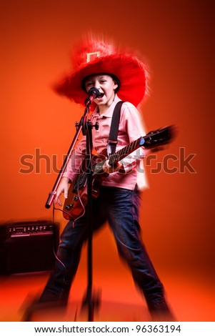 portrait of young boy with a guitar on the stage - stock photo
