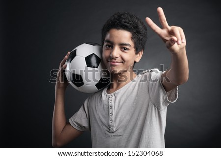 Portrait of young boy with a soccer ball signing victory - stock photo