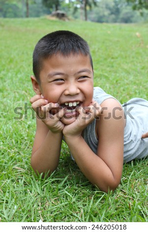 Portrait of young boy with green grass background. - stock photo