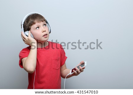 Portrait of young boy with headphones and smartphone on grey background - stock photo