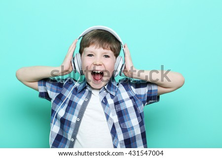 Portrait of young boy with headphones on mint background - stock photo