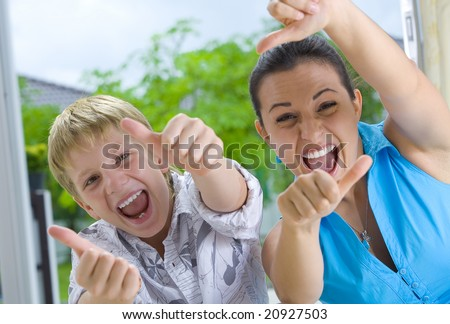 Portrait of young boy with his sister  giving their  thumbs up - stock photo