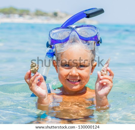 Portrait of young boy with seashells in snorkling equipment swimming in the transparent sea - stock photo
