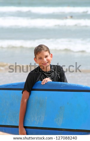 Portrait of  Young Boy with Surfboard smiling directly to the camera - stock photo