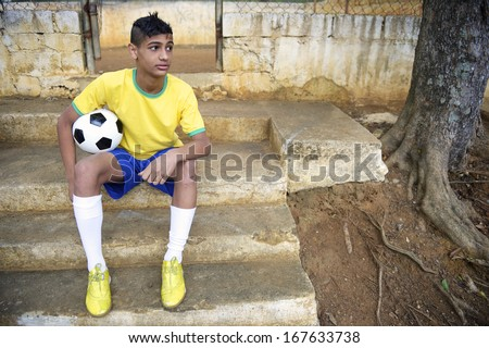 Portrait of young Brazilian soccer player holding football sitting outdoors in his favela neighborhood