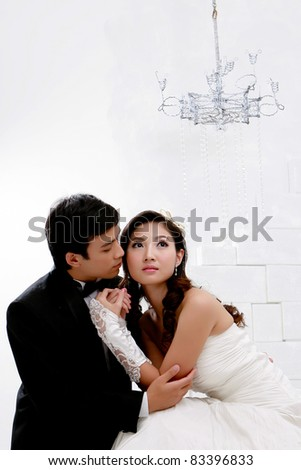 Portrait of young bride and groom in romantic action on white ba - stock photo