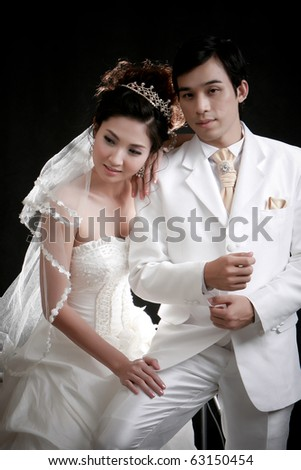 Portrait of young bride and groom in white dress in black background - stock photo