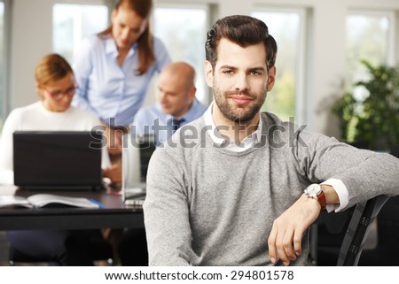 Portrait of young broker sitting at office and looking at camera. Financial experts working at computer at background.