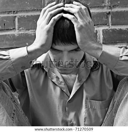 portrait of young brunet guy in depression sitting near red brick wall