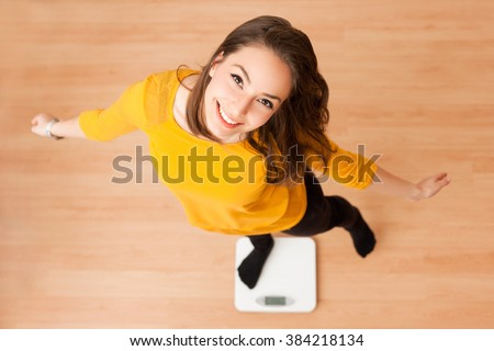 Portrait of young brunette beauty using household scale. - stock photo
