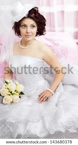 Portrait of young brunette bride with a bouquet on pink - stock photo