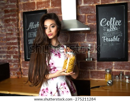 Portrait of young brunette girl cooking in kitchen.Holding a packet of pasta in her hands. Stylishly dressed in white summer flower dress.Cheerful girl smile and showing emotions,ready to cook. - stock photo