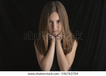 Portrait of young brunette girl resting chin in hands against black background - stock photo