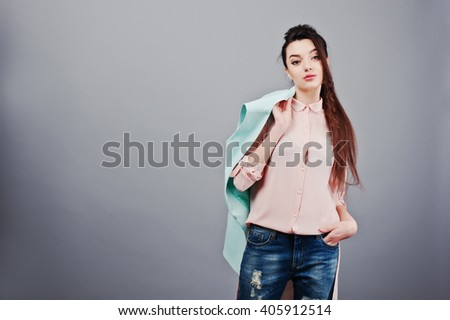 Portrait of young brunette girl wearing in pink blouse, turquoise jacket, ripped jeans. Fashion studio shot - stock photo