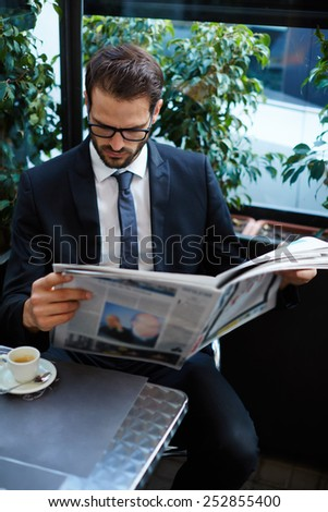 Portrait of young brunette hair businessman sitting in a coffee shop reading a newspaper looking concentrated, handsome business man holding open newspaper sitting in cafe - stock photo