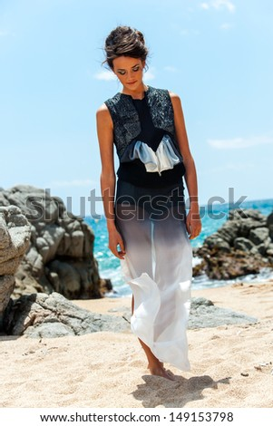 Portrait of young brunette in elegant dress standing on beach. - stock photo