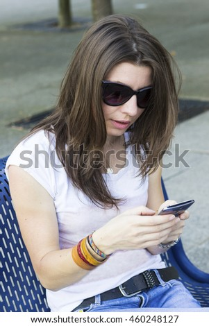 Portrait of young brunette in sunglasses with mobile phone