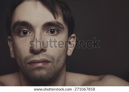 Portrait of young brunette man on a black background - stock photo